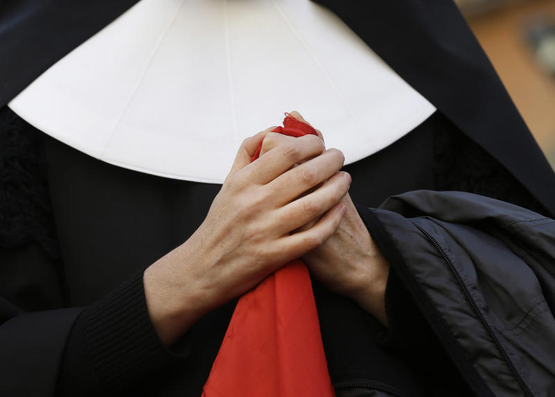 A nun clasps her hands as she waits near the Pope's summer residence of Castel Gandolfo, the scenic town where Pope Benedict XVI will spend his first post-Vatican days and make his last public blessing as pope,Thursday, Feb. 28, 2013. (AP Photo/Luca Bruno)