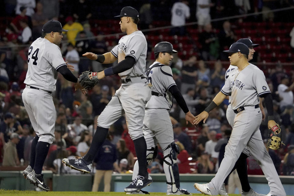 New York Yankees players congratulate each other following their win over the Boston Red Sox in a baseball game at Fenway Park, Friday, Sept. 24, 2021, in Boston. (AP Photo/Mary Schwalm)