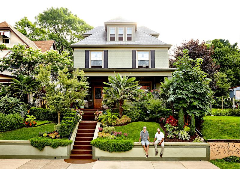 Front yard with multiple plants with two people sitting