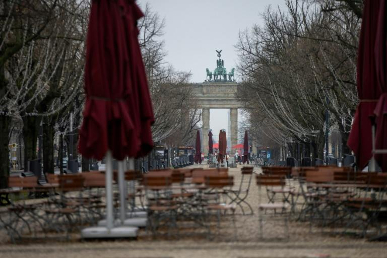 Abandoned cafe chairs and tables on the deserted boulevard leading to landmark Barandenburg Gate in Berlin