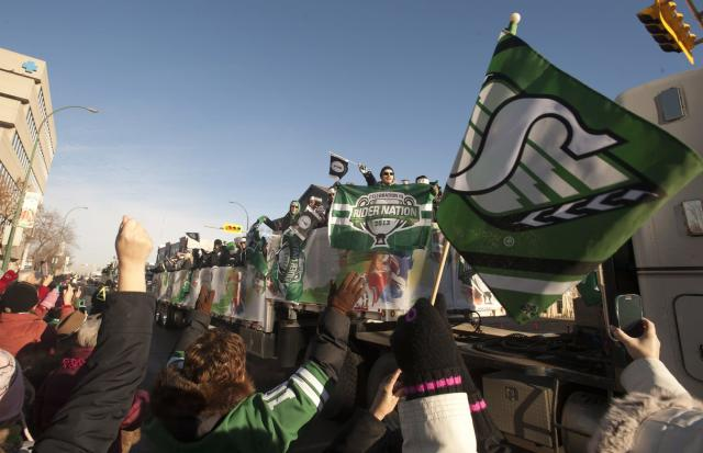 Fans cheer as the Saskatchewan Roughriders float passes them during the Grey Cup parade on Tuesday Nov, 26, 2013, in Regina, Saskatchewan. The Saskatchewan Roughriders defeated the Hamilton Tiger-Cats 45-23 in the 101st CFL Grey Cup football game. (AP Photo/The Canadian Press, Liam Richards)
