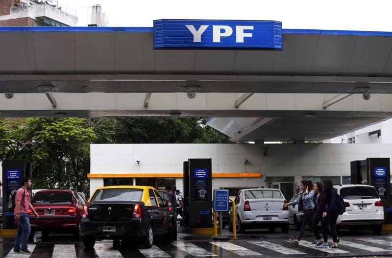 People walk past a YPF petrol station in Buenos Aires