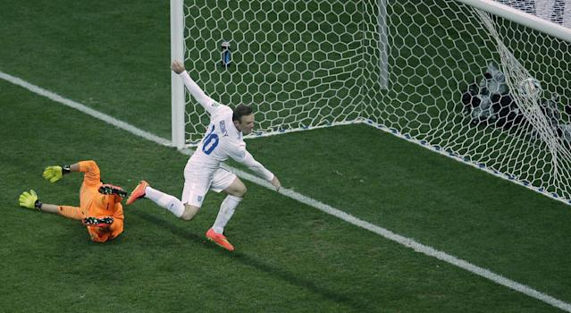 England's Wayne Rooney, center, celebrates scoring his side's first goal past Uruguay's goalkeeper Fernando Muslera, left, during the group D World Cup soccer match between Uruguay and England at the Itaquerao Stadium in Sao Paulo, Brazil, Thursday, June 19, 2014. (AP Photo/Michael Sohn)