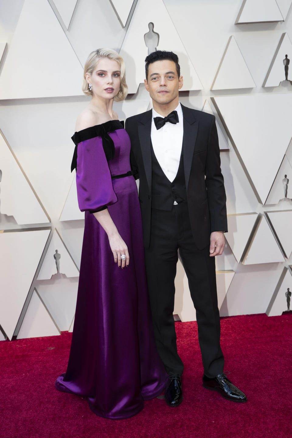 """<p>The """"Bohemian Rhapsody"""" costars and off-screen couple arrived hand-in-hand in a purple Rodarte gown and a classic tuxedo by Saint Laurent. (Image via Getty Images) </p>"""
