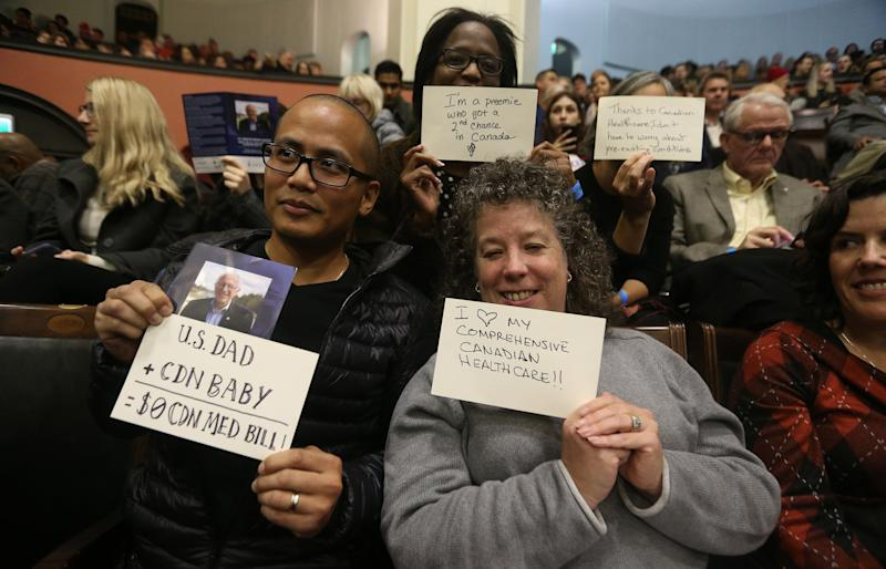 Members of the audience at Sanders' University of Toronto speech hold up cards with positive messages about Canadian health care.