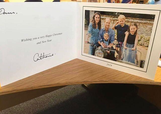 """<p>Air Commodore Dawn McCafferty CBE shared a photograph of a card she received from the Duke and Duchess of Cambridge which features a family photo of the five royals.</p><p>In the photo, William sits on a motorbike with Louis between his legs, while Charlotte and George stand in a sidecar. Kate, dressed in a blue Boden dress, stands alongside her famous family. </p><p><a href=""""https://www.instagram.com/p/B6N6HEaHesf/?utm_source=ig_embed&utm_campaign=loading"""" rel=""""nofollow noopener"""" target=""""_blank"""" data-ylk=""""slk:See the original post on Instagram"""" class=""""link rapid-noclick-resp"""">See the original post on Instagram</a></p>"""