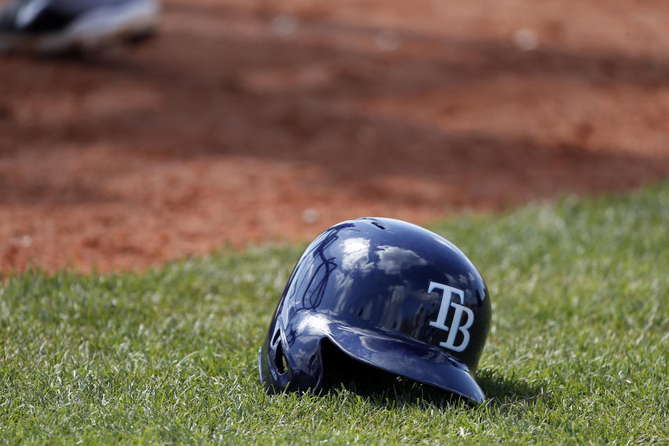 A Tampa Bay Rays helmet sits on the field by the batting cage as players participate in batting practice at baseball spring training in Port Charlotte Fla., Monday March 2, 2015. (AP Photo/Tony Gutierrez)