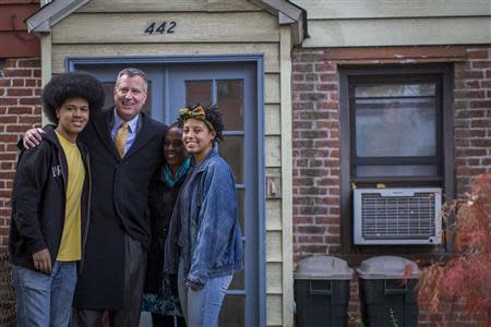 New York City mayor-elect Bill de Blasio poses with his family outside of their Park Slope section of the Brooklyn borough in New York,