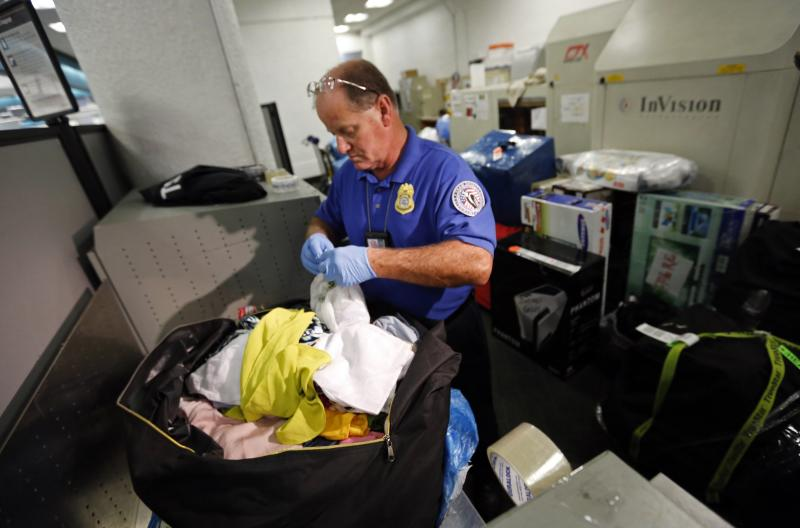 A Transportation Security Administration (TSA) baggage screener checks passengers' luggage at Miami International Airport in Miami, Florida November 1, 2013. TSA Federal Security Director Mark Hatfield on Friday announced a $101 million grant from TSA to install a new automated baggage screening system at Miami International Airport. REUTERS/Joe Skipper (UNITED STATES - Tags: BUSINESS TRANSPORT)