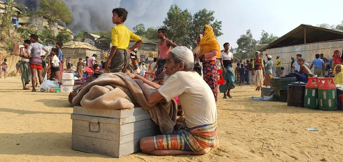 Rohingya refugees salvage their belongings and watch smoke rising following a fire at the Rohingya refugee camp in Balukhali, southern Bangladesh, Monday, March 22, 2021. The fire destroyed hundreds of shelters and left thousands homeless, officials and witnesses said. (AP Photo/ Shafiqur Rahman)