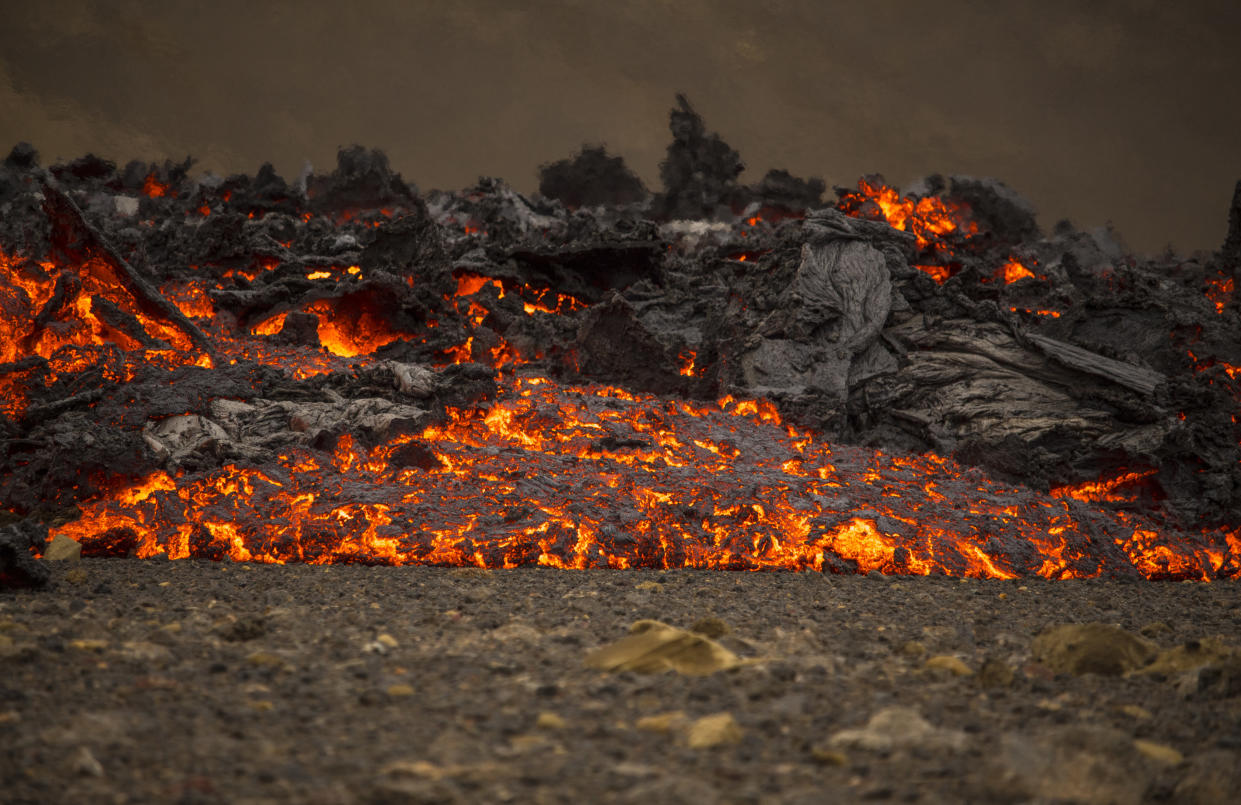 Lava flows from a new fissure on a volcano on the Reykjanes Peninsula in southwestern Iceland, Monday, April 5, 2021. The new fissure has opened up at the Icelandic volcano that began erupting last month, prompting the evacuation of hundreds of hikers who had come to see the spectacle. Officials say the new fissure is about 500 meters (550 yards) long and about one kilometer (around a half-mile) from the original eruption site in the Geldinga Valley (AP Photo/Marco Di Marco)