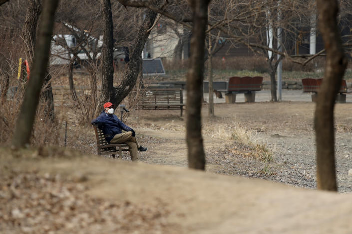 A man wearing a face mask as a precaution against the coronavirus sits on a bench while maintaining social distancing at a park in Seoul, South Korea, Wednesday, Dec. 23, 2020. (AP Photo/Lee Jin-man)