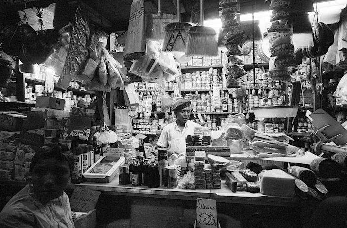 """<p>An employee mans the counter at """"La Marqueta,"""" a Spanish-American marketplace that spans underneath five blocks of Manhattan's upper Park Avenue. </p>"""