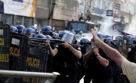Policemen clash with protestors during a demonstration against a possible change in the law to allow for presidential re-election in front of the Congress building in Asuncion