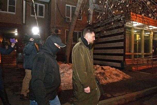 PHOTO: Oleg Navalny (right), accompanied by police officers, walks out after his brother Alexei Navalny's apartment was searched in connection to alleged violations of sanitary and epidemiological rules, on Jan. 27, 2021 in Moscow.   (Alexander Miridonov/Kommersant/Polaris)