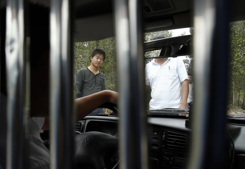 FILE - In this Sept. 9, 2010 file photo, unidentified men block a journalist's vehicle from entering Dongshigu Village, Yinan county, China. Suddenly the guard posts came down and the hired toughs who manned them melted away, restoring an air of freedom this week to the village that authorities turned into a prison to keep blind activist Chen Guangcheng under house arrest for nearly two years. (AP Photo/Andy Wong, File)