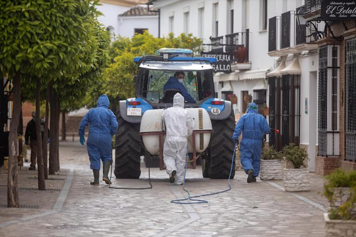 Volunteers use a tractor to disinfect the streets of Zahara de la Sierra in Spain. (Getty Images)