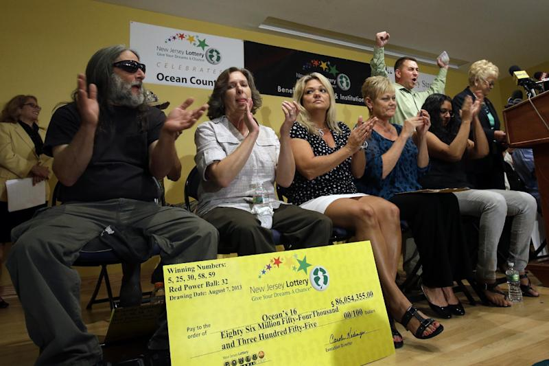 """Lottery winner Brian W. McCarthy raises his arms as other winners applaud Tuesday, Aug. 13, 2013, in Toms River, N.J. The """"Ocean's 16,"""" as a group of 16 public employees on the Jersey shore has been dubbed after snagging one of three winning tickets in last week's $448 million Powerball jackpot, gathered at an afternoon news conference in Toms River, where they work for the Vehicle Services department. The event comes one day after the nine women and seven men claimed their share of the jackpot.(AP Photo/Mel Evans)"""