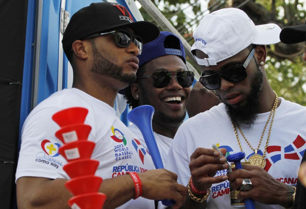 Dominican Republic baseball players, from left, Robinson Cano, Hanley Ramirez and Jose Reyes ride atop a truck during the 2013 World Baseball Classic victory celebration in Santo Domingo, Dominican Republic, Thursday, Nov. 28, 2013. The Dominican Republic team won the third edition of the World Baseball Classic in March, finishing unbeaten in eight games. (AP Photo/Manuel Diaz)
