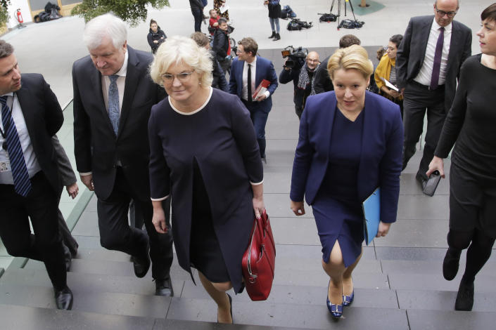 German Interior Minister Horst Seehofer, center left, German Justice Minister Christine Lambrecht, center, and German Minister for Family Affairs, Senior Citizens, Women and Youth, Franziska Giffey, center right, arrive for a news conference in Berlin, Germany, Wednesday, Oct. 30, 2019 on a package of measures against far-right extremism and anti-Semitism. Chancellor Angela Merkel's Cabinet signed off Wednesday on the tightening of gun laws, stricter persecution of hate crime online, and more financial support for initiatives fighting anti-Semitism and far-right extremism. (AP Photo/Markus Schreiber)