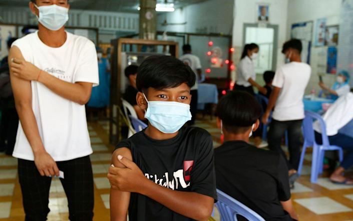 Young Cambodians wait after receiving a dose of China's Sinovac Covid-19 vaccine in Phnom Penh, Cambodia on 1 August 2021 - Mak Remissa/Shutterstock