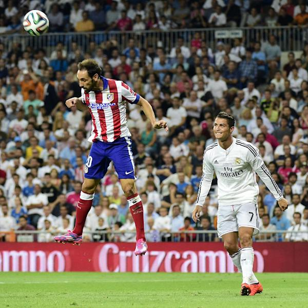 Atletico Madrid's midfielder Juanfran (L) heads the ball next to Real Madrid's Portuguese forward Cristiano Ronaldo during the Spanish Supercup first-leg football match at the Santiago Bernabeu stadium in Madrid on August 19, 2014 (AFP Photo/Gerard Julien)