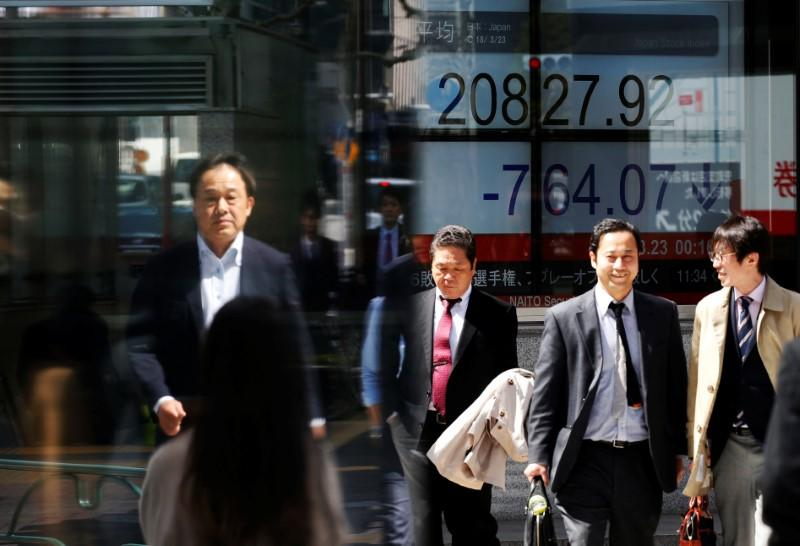 People walk past an electronic board showing Japan's Nikkei average outside a brokerage in Tokyo, Japan, March 23, 2018. REUTERS/Toru Hanai