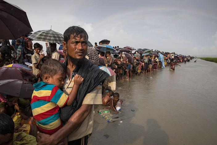 <p>Thousands of Rohingya refugees flee from Myanmar are kept under a tight security by Bangladeshi military after crossing the border in a rice paddy field near Palang Khali, Cox's Bazar, Bangladesh, on October 16, 2017. A rainbow appeared after a brief rainstorm. Well over a half a million Rohingya refugees have fled into Bangladesh since late August during the outbreak of violence in Rakhine state causing a humanitarian crisis in the region with continued challenges for aid agencies. (Photograph by Paula Bronstein/Getty Images) </p>