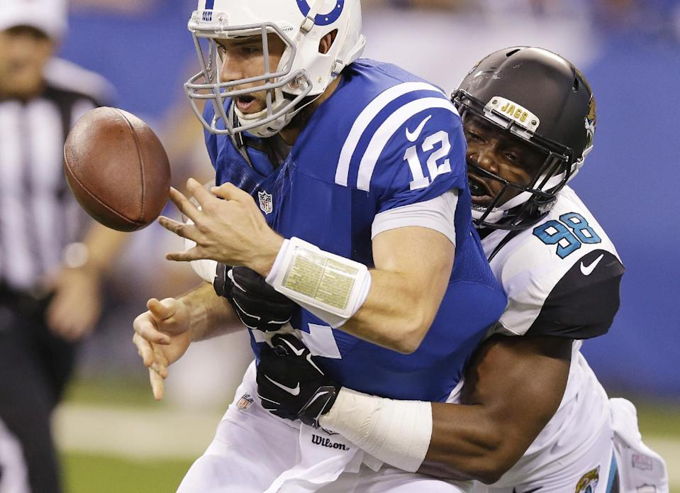 Indianapolis Colts quarterback Andrew Luck (12) fumbles after being hit Jacksonville Jaguars defensive end Chris Smith (98) during the first half of an NFL football game Sunday, Nov. 23, 2014 in Indianapolis. (AP Photo/Michael Conroy)
