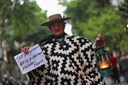 "A man wearing traditional Gaucho clothes holds a lantern during a protest against a cost increase in public and utility services in Buenos Aires, Argentina, January 10, 2019. The sign on the left reads ""I am a pensioner, We can't take it anymore - (City of) Navarro, present"". REUTERS/Marcos Brindicci"