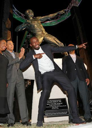 Olympic champion Usain Bolt (C) poses after the unveiling of his statue at the Statue Park at the National Stadium, in Kingston, Jamaica December 3, 2017. REUTERS/Gilbert Bellamy