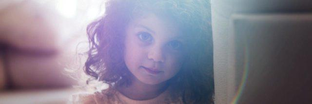 Young girl with curly brown hair wearing an orange top leans against a wall and looks directly at the camera