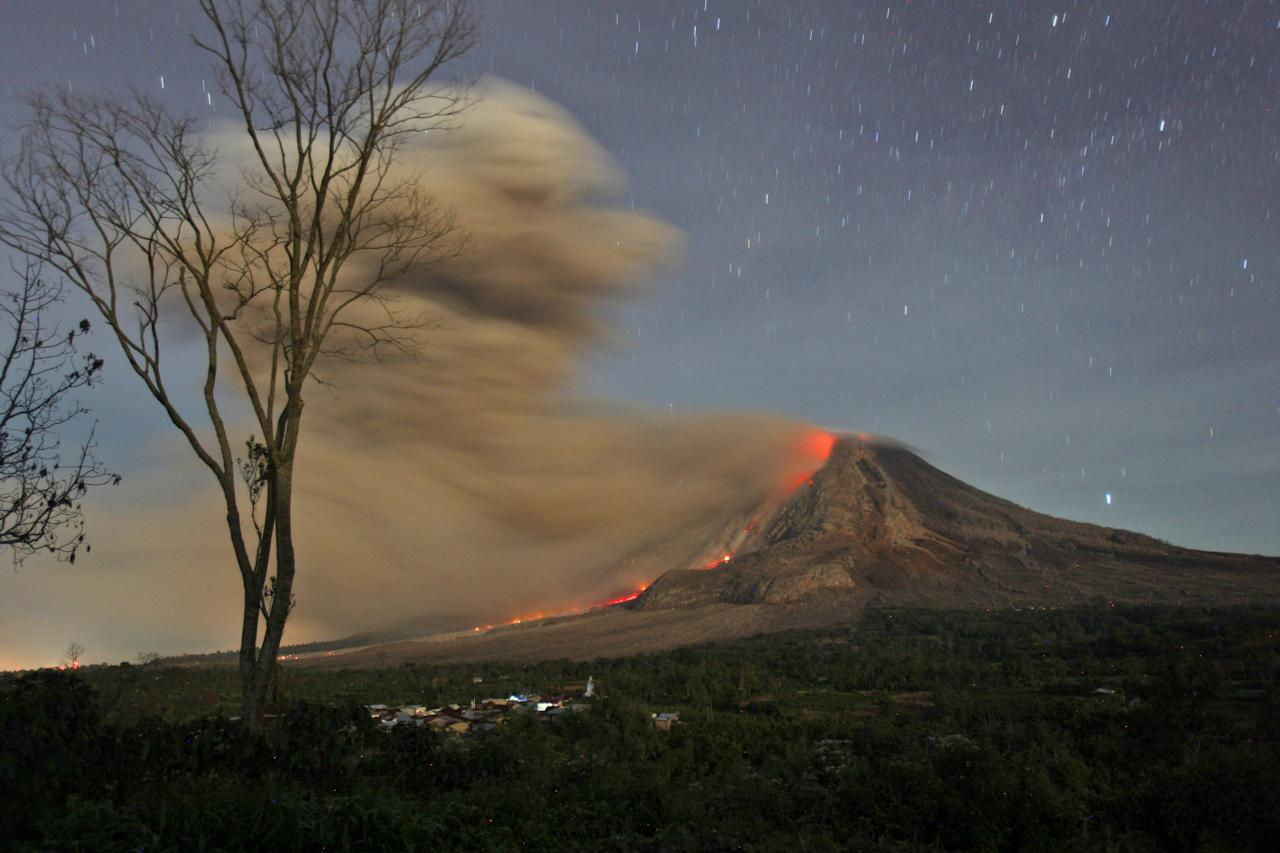 In this photo made with a slow shutter speed, Mount Sinabung spews hot lava and volcanic ash as seen from Jeraya, North Sumatra, Indonesia, early Tuesday, Oct. 14, 2014. Mount Sinabung, among about 130 active volcanoes in Indonesia, has sporadically erupted since 2010 after being dormant for 400 years. (AP Photo/Binsar Bakkara)