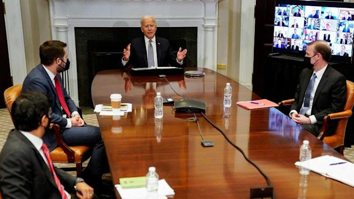 President Biden and three advisers sit around the table and business leaders join with a video link