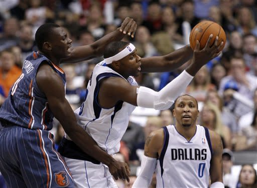 Charlotte Bobcats center Bismack Biyombo (0), of the Republic of the Congo, defends against a pass by Dallas Mavericks' Brendan Haywood, center, as Shawn Marion (0) looks on in the first half of an NBA basketball game Thursday, March 15, 2012, in Dallas. (AP Photo/Tony Gutierrez)