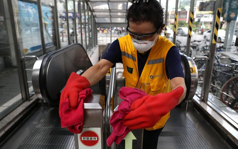 A disinfection worker sprays anti-septic solution at the subway station in Seoul - Getty
