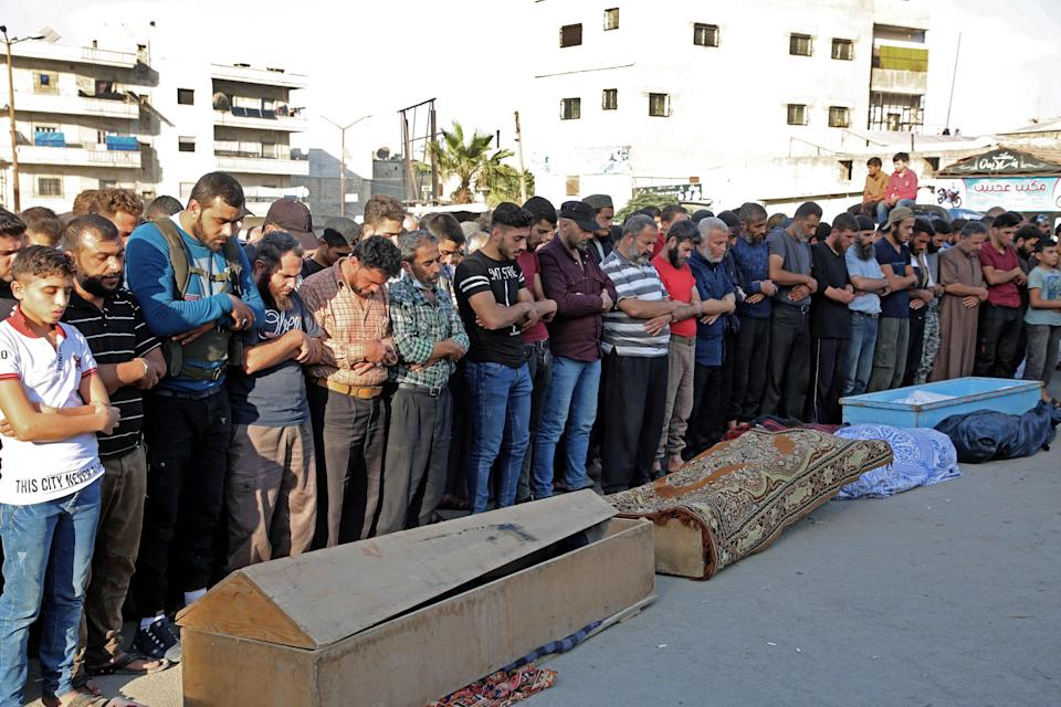Syrians take part in the funeral of 10 fighters with the Turkey-backed Faylaq al-Sham rebel faction in Syria, in Idlib, on October 26, 2020, following their death in a Russian air strike.  (Photo by MOHAMMED AL-RIFAI/AFP via Getty Images) (AFP via Getty Images)