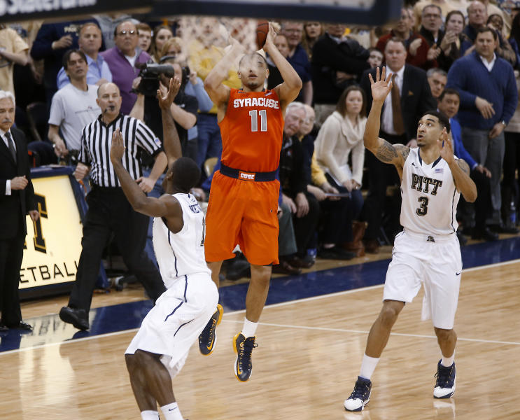 Syracuse's Tyler Ennis (11) shoots 3-pointer between Pittsburgh's Cameron Wright (3) and Josh Newkirk, left, in the final second of an NCAA college basketball game Wednesday, Feb. 12, 2014, in Pittsburgh. The shot went in and Syracuse won 58-56. (AP Photo/Keith Srakocic)