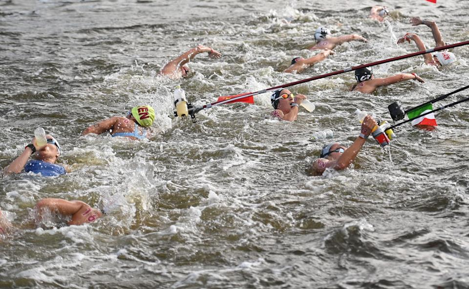 Competitors take refreshments at a feed station in the women's 10km marathon swimming event during the Tokyo 2020 Olympic Games at the Odaiba Marine Park in Tokyo on August 4, 2021. (AFP via Getty Images)