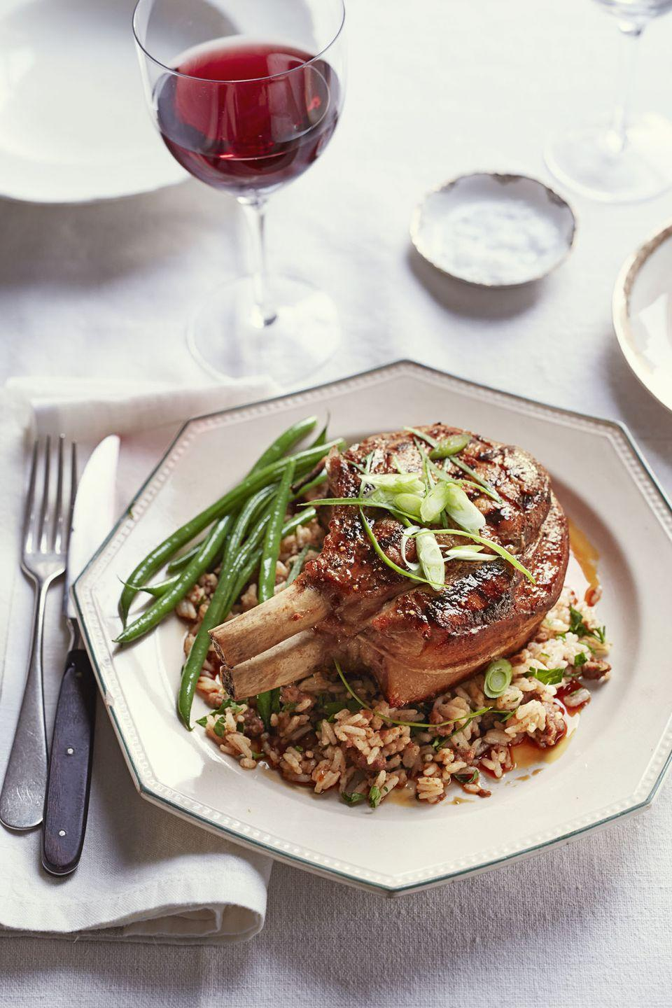 """<p>Ditch those dinner reservations and cook up this flavor-packed dinner, instead.</p><p><a href=""""https://www.goodhousekeeping.com/food-recipes/a16964/sweet-n-sticky-pork-chops-dirty-rice-recipe-ghk0315/"""" rel=""""nofollow noopener"""" target=""""_blank"""" data-ylk=""""slk:Get the recipe for Sweet 'n' Sticky Pork Chops with &quot;Dirty&quot; Rice »"""" class=""""link rapid-noclick-resp""""><em>Get the recipe for Sweet 'n' Sticky Pork Chops with """"Dirty"""" Rice »</em></a></p>"""