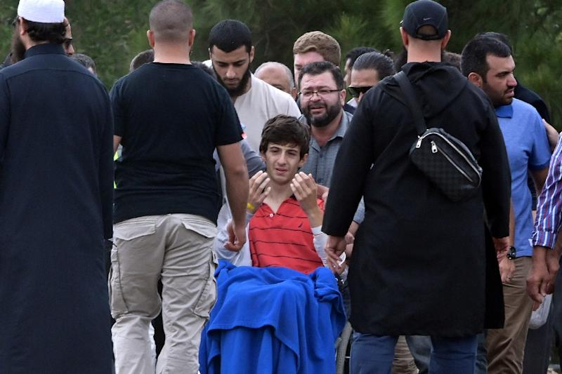 In a powerful scene, the son of a victim sat in a wheelchair, his hands held aloft as he prayed (AFP Photo/Anthony WALLACE)