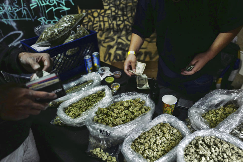 FILE - In this April 15, 2019, file photo, a vendor makes change for a marijuana customer at Rev-Up a cannabis marketplace in Los Angeles. An alliance of large cannabis businesses in the growing global marketplace has a message for the public: We're good corporate citizens. The 45-member Global Cannabis Partnership that includes Canopy Growth Corp. and other major companies issued guidelines Tuesday, June 18, 2019, aimed at minimizing greenhouse gas emissions and promoting ethical conduct and responsible pot use. (AP Photo/Richard Vogel)