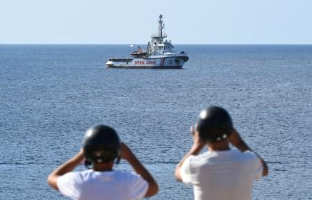 Tourists take pictures of the Spanish migrant rescue ship Open Arms close to the Italian shore in Lampedusa
