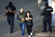 "Georgian police officers escorts a woman who escaped from a bank where an armed assailant has taken several people hostage, in the town of Zugdidi in western Georgia, Wednesday, Oct. 21, 2020. An armed assailant took several people hostage at a bank in the ex-Soviet nation of Georgia on Wednesday, authorities said. The Georgian Interior Ministry didn't immediately say how many people have been taken hostage in the town of Zugdidi in western Georgia, or what demands the assailant has made. Police sealed off the area and launched an operation ""to neutralize the assailant,"" the ministry said in a statement. (AP Photo/Zurab Tsertsvadze)"
