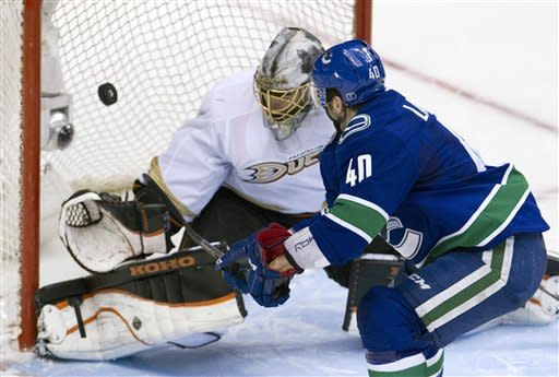Vancouver Canucks center Maxim Lapierre (40) makes the game-winning goal past Anaheim Ducks goalie Jonas Hiller (1) during a shootout of an NHL hockey game in Vancouver, British, Columbia, on Tuesday, April, 3, 2012. (AP Photo/The Canadian Press, Jonathan Hayward)
