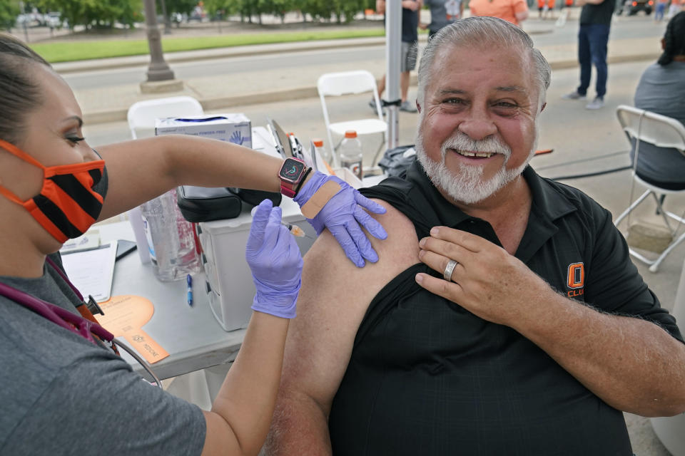 Mick Mitchell, of Edmond, Okla., smiles as he gets a COVID-19 vaccination shot from Dondie Hess, left, of the Oklahoma State University Center for Health Sciences, at a vaccination event before an NCAA college football game between Missouri State and Oklahoma State, Saturday, Sept. 4, 2021, in Stillwater, Okla. Oklahoma State University announced that it will host COVID-19 vaccine clinics before home football games this fall to make it easier for students, fans and the community to receive a vaccine. (AP Photo/Sue Ogrocki)