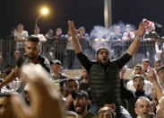 Palestinians celebrates after Israel's police removed barricades in a plaza outside of Jerusalem's Old City, Sunday, April 25, 2021.Israeli police late Sunday removed barricades outside Jerusalem's Old City that had prevented Muslims from meeting in a traditional gathering spot during the holy month of Ramadan. The barricades have sparked nightly clashes between Palestinian protesters and Israeli police, and their removal appeared to be aimed at easing the tensions. (AP Photo/Ariel Schalit)