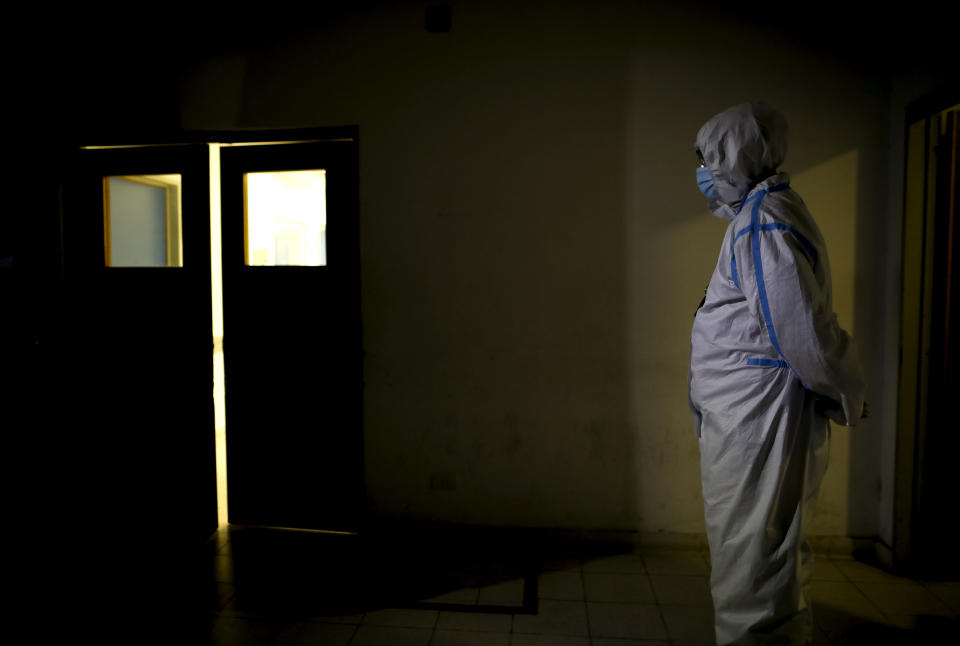 A healthcare worker stands outside Llavallol Dr. Norberto Raúl Piacentini Hospital in Lomas de Zamora, Argentina, Saturday, May 1, 2021, amid the new coronavirus pandemic. Many doctors try to stay out of the political disputes, instead urging people to stick to measures aimed at preventing the spread of COVID-19. (AP Photo/Natacha Pisarenko)