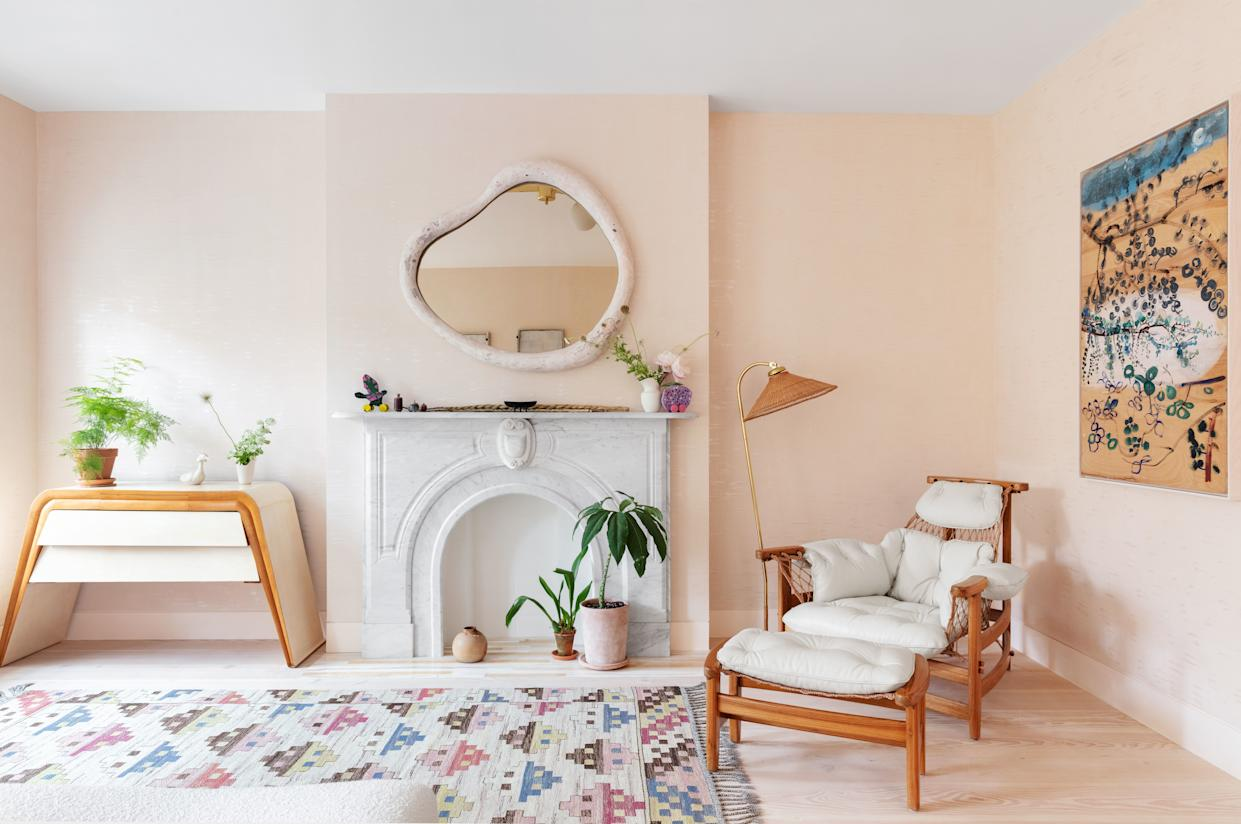 """<div class=""""caption""""> In the master bedroom, a custom <a href=""""https://www.r-and-company.com/designers/rogan-gregory/"""" rel=""""nofollow noopener"""" target=""""_blank"""" data-ylk=""""slk:Rogan Gregory"""" class=""""link rapid-noclick-resp"""">Rogan Gregory</a> mirror hangs above the original carved-marble fireplace. 20th-century Swedish flat-weave carpet; on right wall, art by Bill Lynch. </div>"""