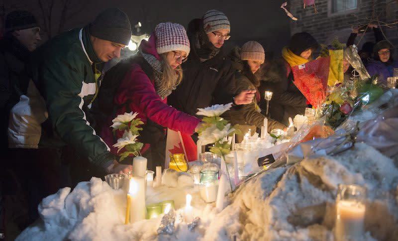 <p>People place candles on the snow in a vigil in Quebec City for those killed in a massacre Sunday. Photo from The Canadian Press </p>